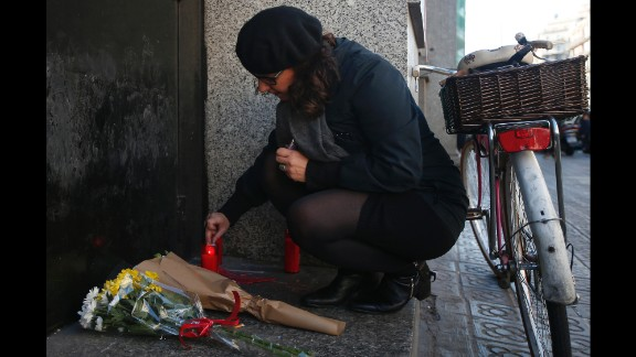 A woman lights a candle outside the French Consulate in Barcelona, Spain, on November 14.