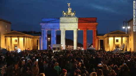 The Brandenburg Gate in Berlin, Germany stands illuminated in the colors of the French flag as people arrive to lay candles and flowers at the gate of the adjacent French Embassy.
