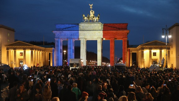The Brandenburg Gate in Berlin stands illuminated in the colors of the French flag as people lay candles and flowers at the adjacent French Embassy on November 14.