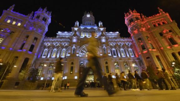 People cross the street past the Cibeles Palace, Madrid