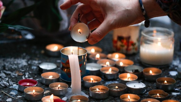 A woman lights candles at a memorial near the Bataclan theater in Paris on November 14.