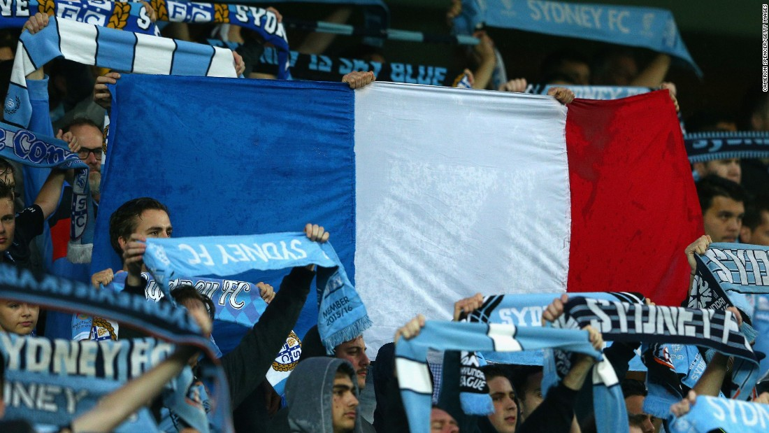 Sydney FC fans hold up a French flag during a moments silence for victims of the Paris terror attacks prior its match against Melbourne Victory at Allianz Stadium in Sydney.