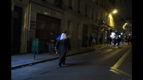 A man wearing a French flag walks through the streets of Paris on November 14. French President Francois Hollande has declared a state of emergency.