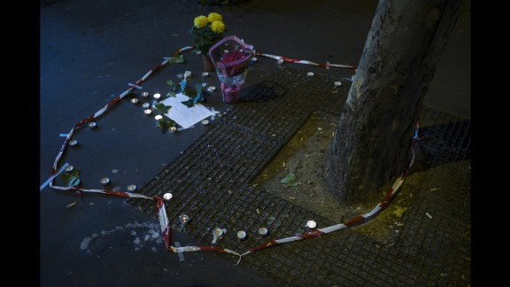 Candles and flowers are seen on November 14 at the spot where a victim died on the Rue de la Fontaine au Roi. Five people were killed in a shooting outside a bar in Paris