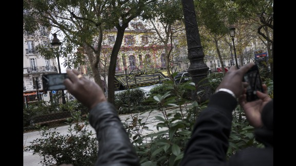 People take pictures on November 14 near the Bataclan concert hall, where more than 80 people were killed.