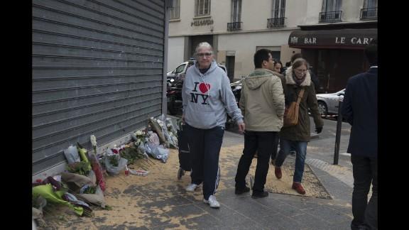A woman walks past a memorial in Paris