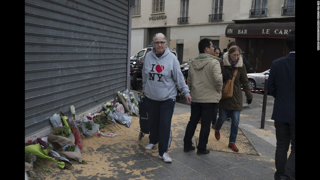 A woman walks past a memorial in Paris' 10th district November 14.