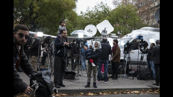 A family stands among TV crews set up on November 14 near the Bataclan.