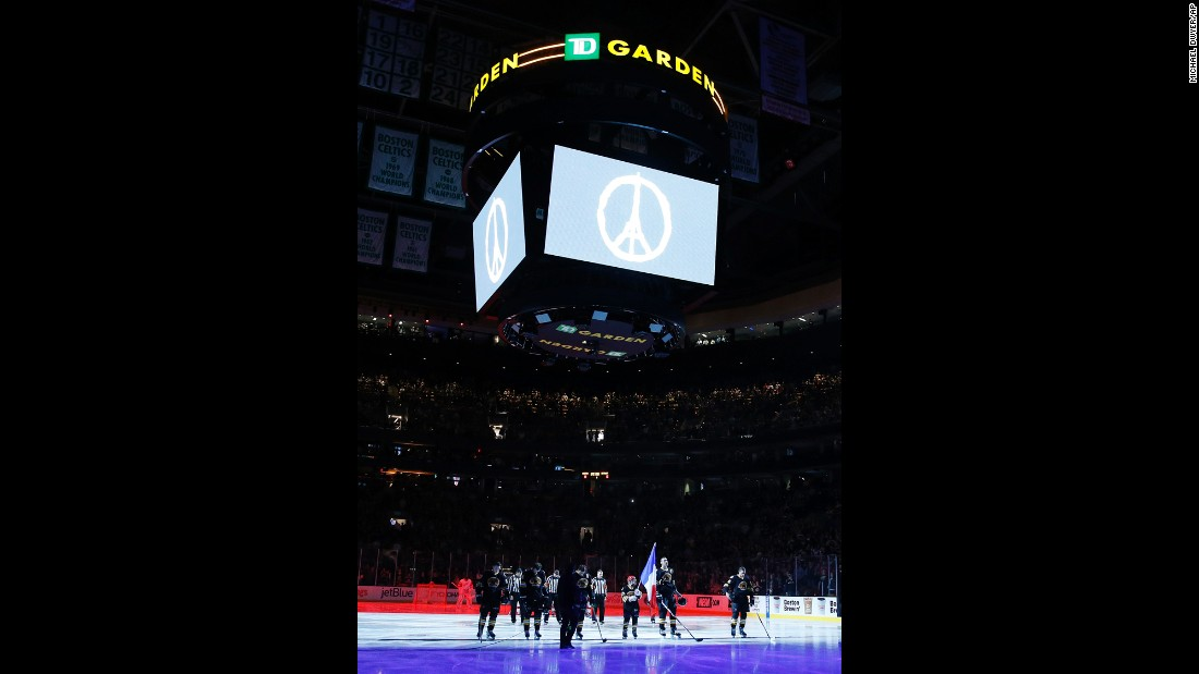 The Boston Bruins and the Detroit Red Wings stand on the ice while the French national anthem is played before an NHL hockey game in Boston. The symbol for 'Peace for Paris' appears above the rink.