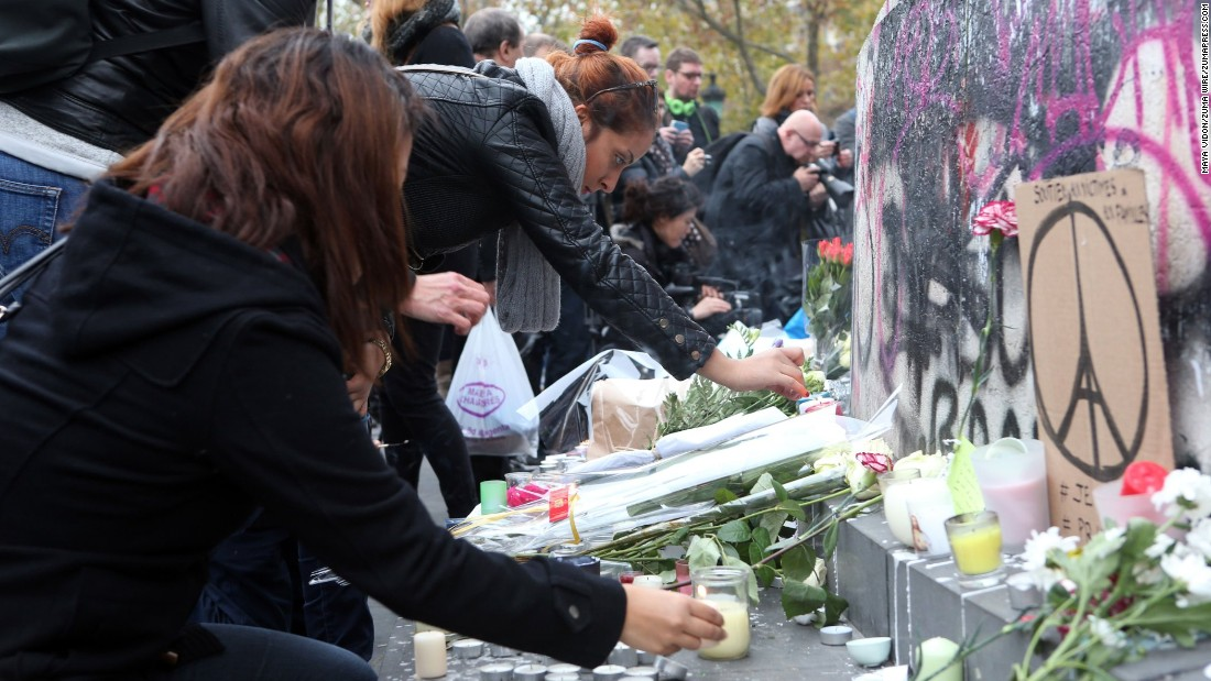 People gather around the statue of Marianne, symbol of the French Republic, to lay flowers and light candles in tribute to the victims of deadly attacks that struck Paris.