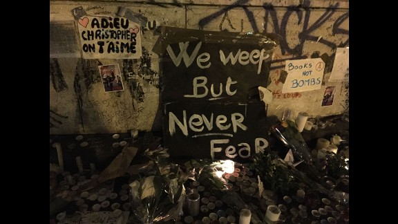 """Candles, flowers and signs are placed at a makeshift memorial in Paris. French President Francois Hollande has called the deadly attacks """"an act of war."""" ISIS claimed responsibility."""