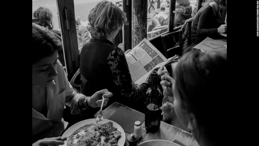 "A woman reads a publication with bolded and capitalized letters spelling out l'horreur, while people all around her fork pieces of food from their plates. ""People were standing outside, having their brunch or whatever, and literally 100 meters away, eight hours before, 18 people (were) being killed,"" Majoli said.<br />"