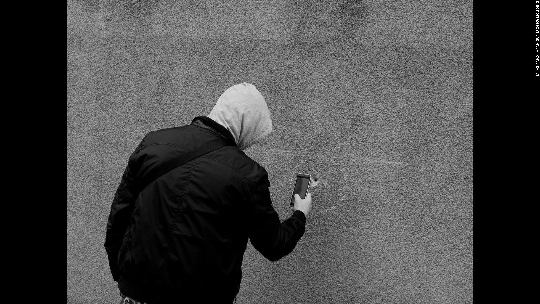 "A man uses his phone to take a photo of a bullet hole near Le Carillon and Le Petit Cambodge. The photographer says he tries to capture the theatrical side of life, using light in a way that ""creates this idea of fiction, of theater.""<br />"