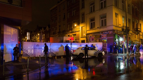 Belgian police cordon off a street during a police raid in connection with the November 13 deadly attacks in Paris, in Brussels