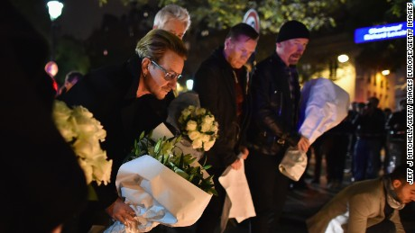 Bono, left, and members of U2 place flowers near the Bataclan Theatre in Paris on Saturday.