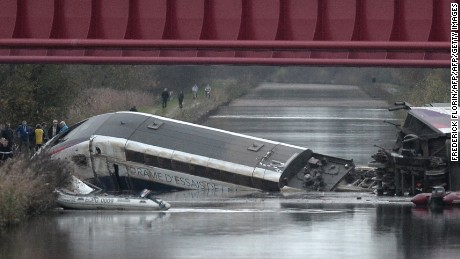 Rescuers arrive at the scene where a high-speed train derailed and crashed into a canal in eastern France on Saturday.