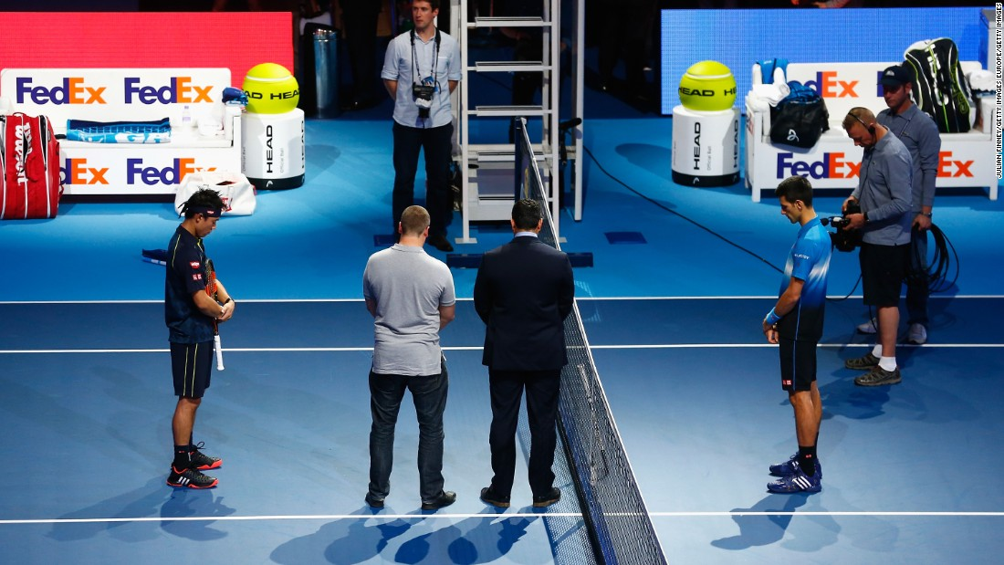 Novak Djokovic (R) of Serbia and Kei Nishikori of Japan observe a minute's silence before their group stage match at the ATP World Tour Finals in London.