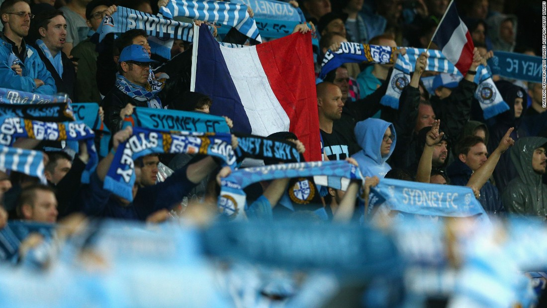 Sydney FC fans hold up a French flag during a moments silence for victims of the Paris terror attacks prior to their team's A-League football match against Melbourne Victory.
