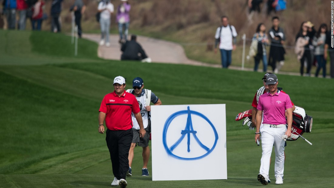 Patrick Reed (L) of the US and Kristoffer Broberg (R) of Sweden pass a sign placed to commemorate the victims of the Paris attacks during the Shanghai Masters.