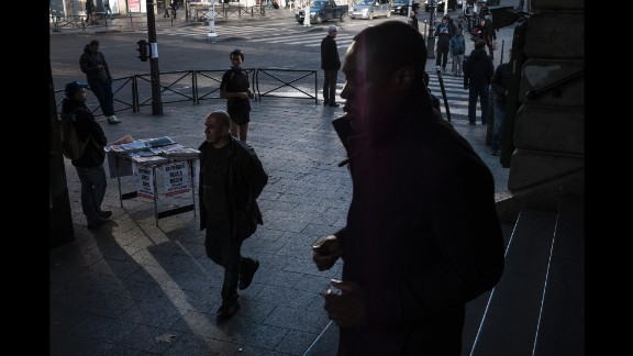 """A man sells newspapers on Sunday, November 15, at the Barbes-Rochechouart Metro station in one of the Paris neighborhoods with the highest foreign-born population. The headlines read """"The War against Daech / ISIS"""" and """"The Day After."""""""