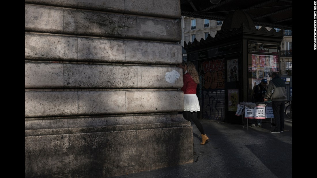 People walk past a man selling newspapers near the Barbes-Rochechouart Metro station on November 15.