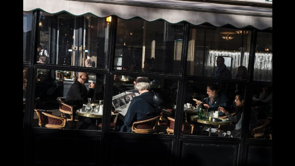 A woman reads a newspaper in the Cafe Les Deux Magots on November 15 In the St. Germain neighborhood of Paris.