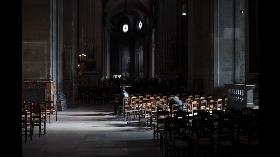 People sit inside the St. Sulpice Catholic church on November 15 in Paris.