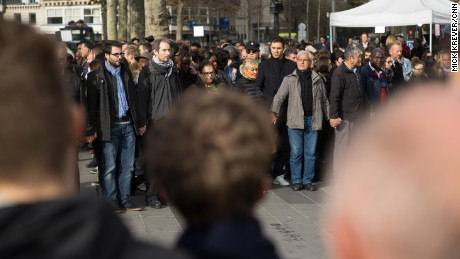 In honor of the victims of Friday's terror attacks, people observe a minute of silence in the Place de la Republique in Paris on Monday, November 16.