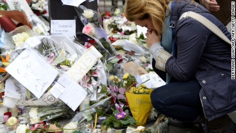 A woman takes a moment to pay her respects ahead of a minute of silence on November 16, 2015 at the Bataclan concert hall in Paris.