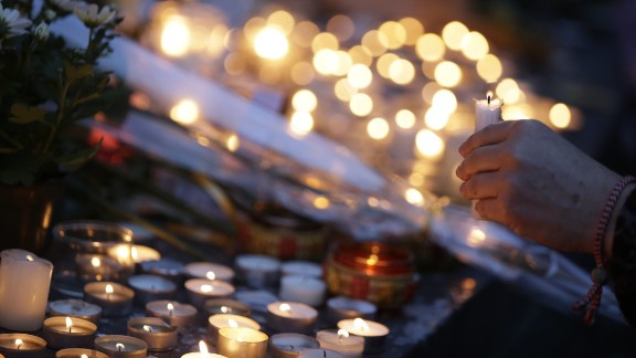 People place candles for the victims of a series of coordinated attacks in and around Paris, at the Place de la Republique square in Paris on November 14, 2015. At least 128 people were killed in the Paris attacks on the evening of November 13, with 180 people injured, 80 of them seriously, police sources told AFP.  AFP PHOTO / KENZO TRIBOUILLARD       (Photo credit should read KENZO TRIBOUILLARD/AFP/Getty Images)