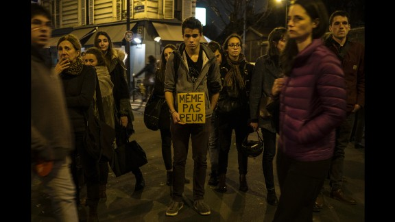 """A young man in Paris on November 16 holds a sign that reads """"Not even afraid"""" in the neighborhood of Le petit Cambodge, a restaurant that was hit in the attacks."""