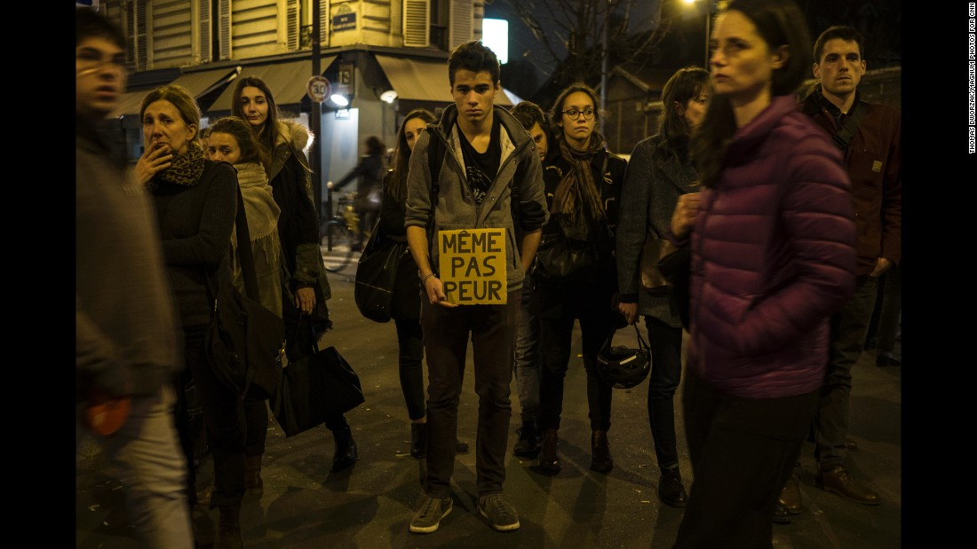 "A young man in Paris on November 16 holds a sign that reads ""Not even afraid"" in the neighborhood of Le petit Cambodge, a restaurant that was hit in the attacks."
