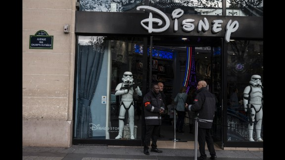 Security guards stand outside a Disney store on Champs Elysees in Paris on November 16.