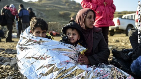 A Syrian family waits after arriving on the Greek island of Lesbos along with other migrants and refugees, on November 17, 2015, after crossing the Aegean Sea from Turkey.  At least eight people drowned when a boat carrying migrants from Turkey sank off the Greek island of Kos, the coastguard said on November 17, 2015. They were the latest of nearly 3,500 deaths at sea this year among people making desperate bids to flee war and poverty and to reach Europe, according to UN figures. European leaders tried to focus on joint action with Africa to tackle the migration crisis, as Slovenia became the latest EU member to act on its own by barricading its border. AFP PHOTO/BULENT KILIC        (Photo credit should read BULENT KILIC/AFP/Getty Images)