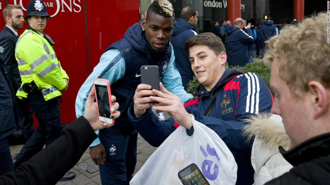 France midfielder Paul Pogba (C) stops to have a selfie taken with a supporter.