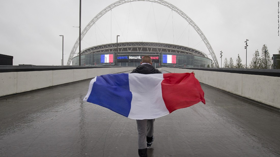 A French football fan, draped in the national flag, walks towards Wembley Stadium in London, ahead of the international friendly football match between England and France.