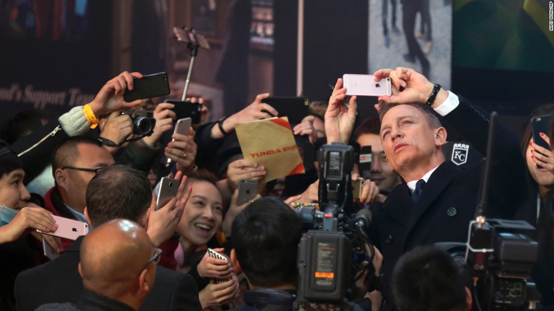 "Actor Daniel Craig uses a fan's cell phone to take a selfie in Beijing on Thursday, November 12. Craig was on the red carpet for his latest James Bond movie, ""Spectre."""