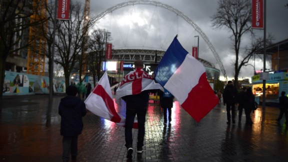 A supporter carries a French and an English flag as he makes his way towards Wembley before the game.