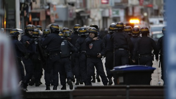 Police take positions during the raid.