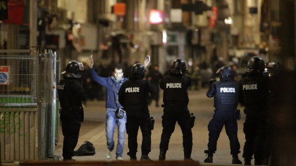 A man approaches a line of police officers during the raid.