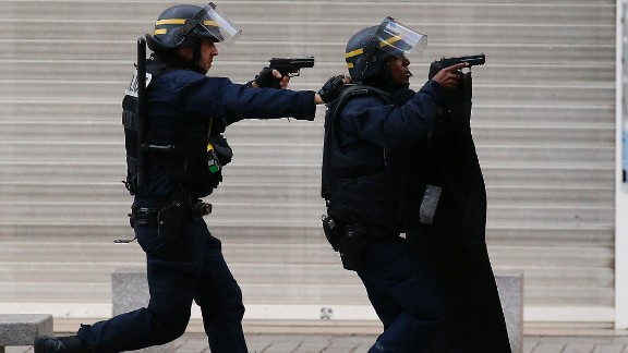 Armed police  operate in Saint-Denis, a northern suburb of Paris, Wednesday, Nov. 18, 2015. Police say two suspects in last week's Paris attacks, a man and a woman, have been killed in a police operation north of the capital. Two police officers have been injured in the standoff. Police have said the operation is targeting the suspected mastermind of last week's attacks, believed to be holed up in an apartment in Saint-Denis with several other heavily armed suspects. (AP Photo/Francois Mori)