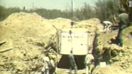 Workers excavate the buried moving van where 27 hostages were trapped.
