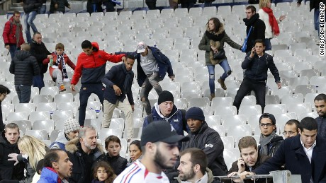 Fans climb down the seats of the Stade de France after the match.