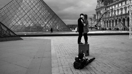 A couple poses in embrace for a photographer in front of the entrance of the Louvre museum in Paris, France three days after coordinated terrorist attacks struck the heart of the French capital. The Louvre reopened Monday afternoon.