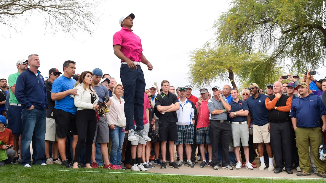 Tiger Woods leaps above the gallery to see the eighth green during the first round of the Phoenix Open on Thursday, January 29.