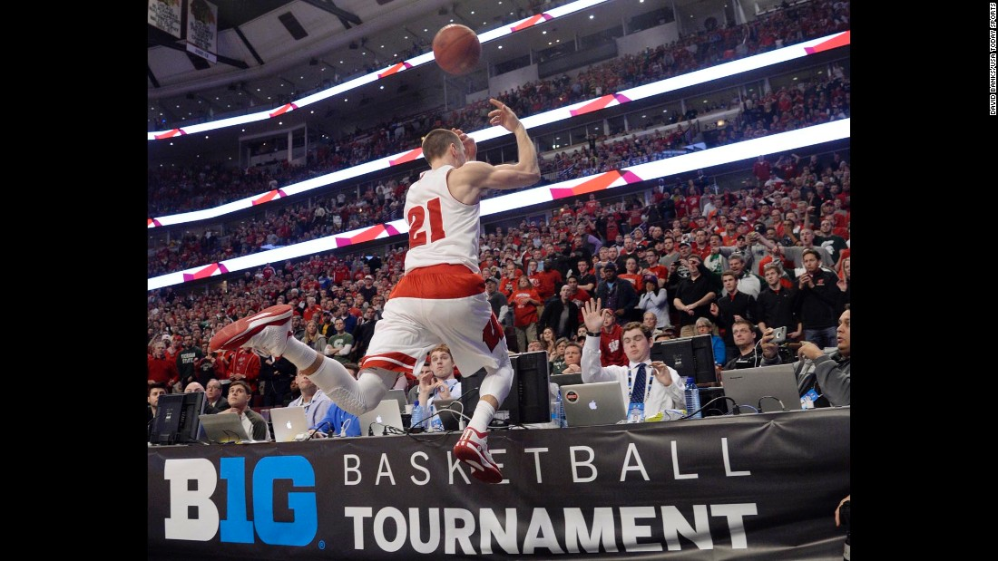 Wisconsin guard Josh Gasser dives into press row to keep a loose ball inbounds during the Big Ten championship game Sunday, March 15, in Chicago. The Badgers defeated Michigan State 80-69 and were later named a No. 1 seed in the NCAA Tournament.