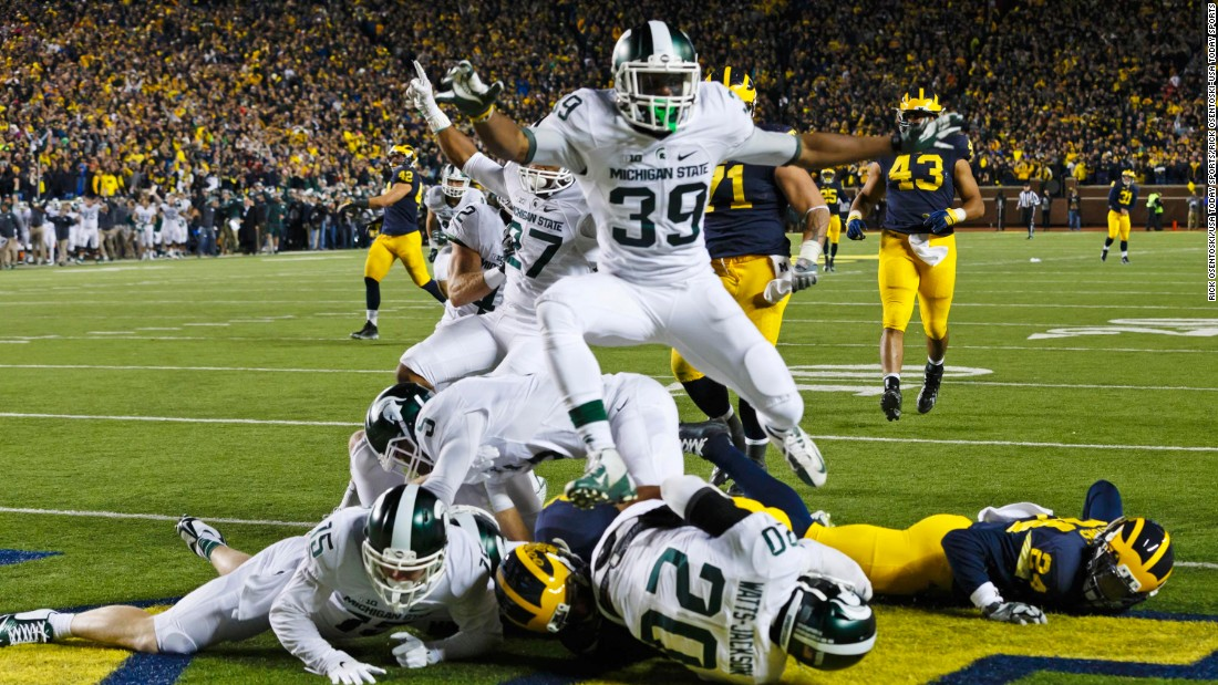 "Michigan State players crash into the end zone after Jalen Watts-Jackson scored an improbable touchdown to defeat Michigan on Saturday, October 17. Michigan looked to have the game in hand until fumbling on a punt play with 10 seconds left. Watts-Jackson <a href=""http://bleacherreport.com/articles/2580146-michigan-state-wins-on-walk-off-td-after-michigan-punter-fumbles-on-final-play"" target=""_blank"">returned the ball</a> for a 27-23 victory."