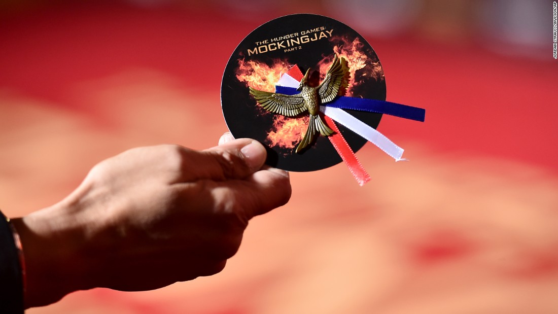 "The French tricolor is attached to one of the pins that were handed out at the Los Angeles premiere of the new ""Hunger Games"" movie on Monday, November 16."