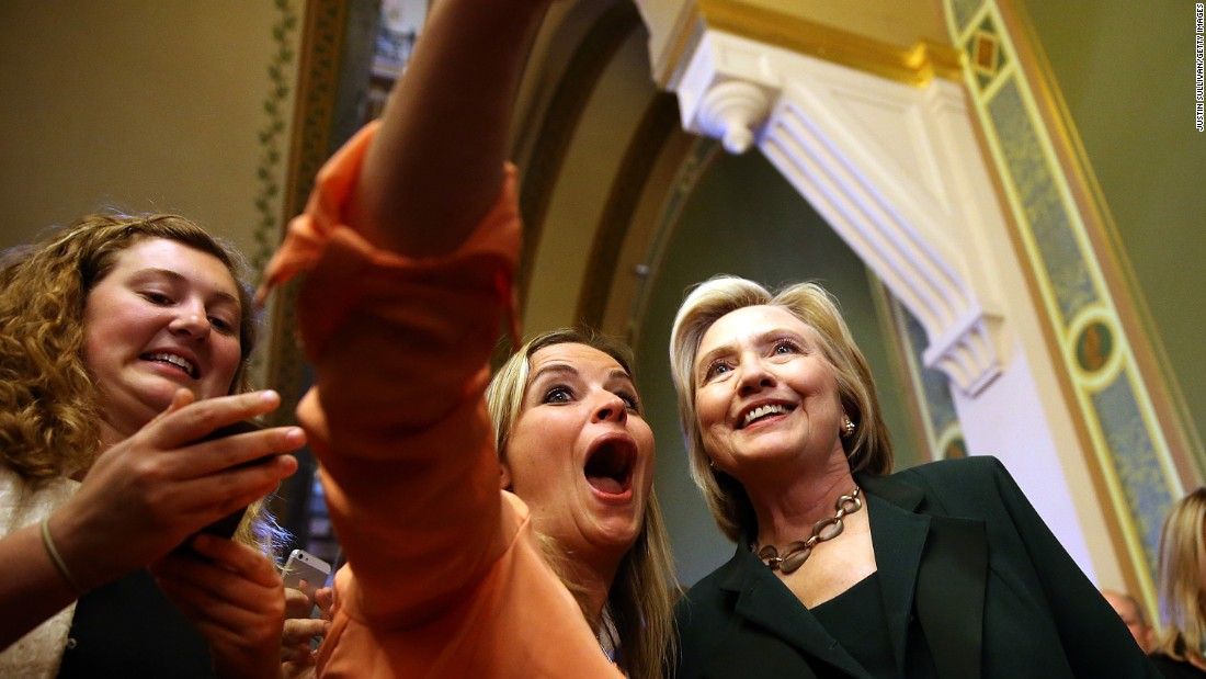 Democratic presidential candidate Hillary Clinton, right, stops for a selfie after meeting with members of the Iowa state legislature on Wednesday, April 15.
