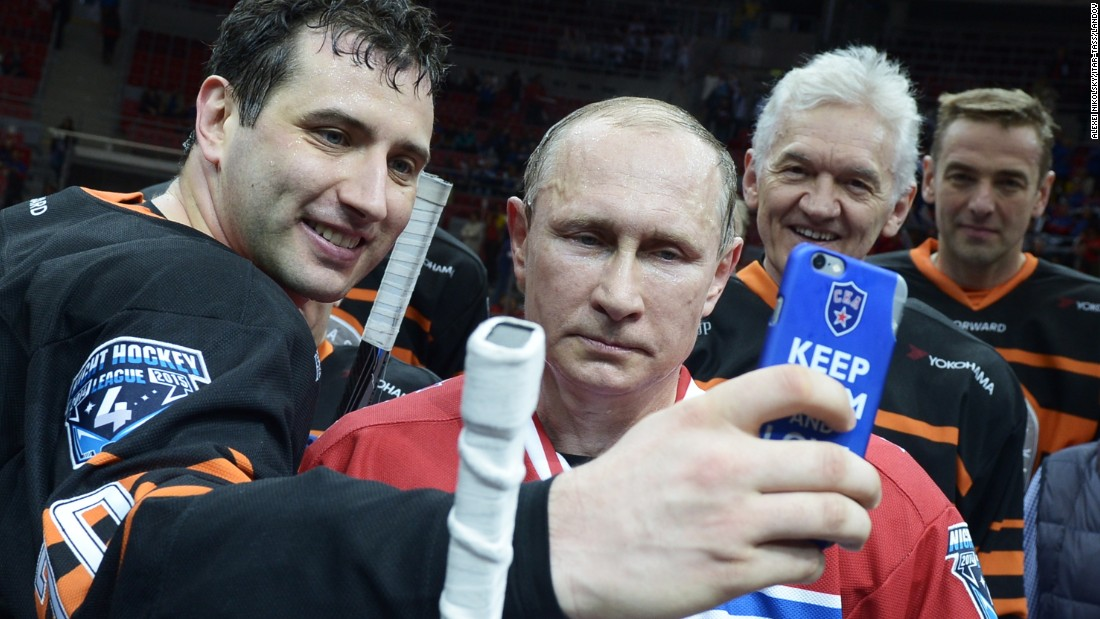 Russian President Vladimir Putin, second from left, looks at the phone of Roman Rotenberg while Rotenberg takes a selfie on Saturday, May 16. Rotenberg, the vice president of the hockey club SKA St. Petersburg, had just played hockey with Putin and other prominent officials in Sochi, Russia.